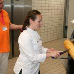 Die angehende Konditormeisterin Eva Maria Hofer schneidet ihren Baumkuchen an, neben ihr Backstubenleiter Werner Wolf.
