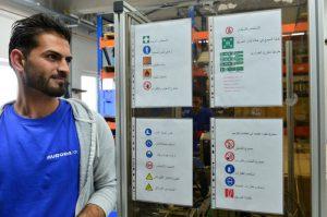 Rwat Darwis aus Syrien arbeitet zurzeit in der Düsenmontage der Firma Aurora Konrad G. Schulz in Mudau. Die Sicherheitshinweise hängen dort in mehreren Sprachen. Foto: IHK Rhein-Neckar/Rinderspacher