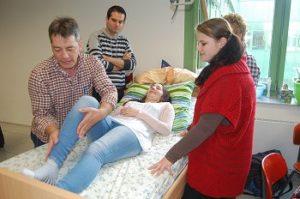 Reinhard Leitner demonstriert zukünftigen Altenpflegern das kinästethische Hochrücken eines Patienten. Im Sinne von Prävention wird von Anfang an Wert auf gesundheitsschonendes Arbeiten gelegt.
